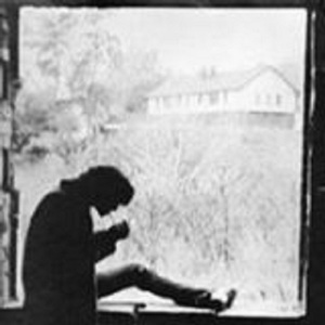 John Calabro'languidly strikes a match to light his cigarette while sitting on the unfinished window frame of the Ghost of Bayview in 1972